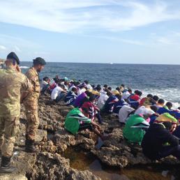 Migranti in preghiera a Lampedusa (Ansa)