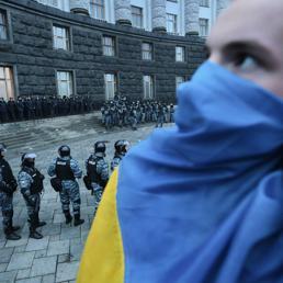 Nella foto un dimostrante con la bandiera dell'Ucraina sulla bocca durante le manifestazioni e gli scontri di domenica contro la Polizia (Space24)