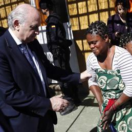 Il ministro Jorge Fernandez Diaz con una donna immigrata in un centro per rifugiati in Spagna (Reuters)