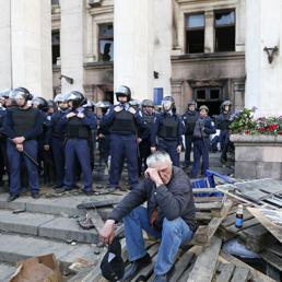 Un uomo seduto davanti alla Casa dei sindacati dei sindacati di Odessa dopo il rogo del 2 maggio (Reuters)