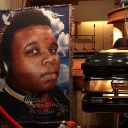 Un'immagine di Michael Brown accanto alla bara nel giorno del suo funerale, il 25 agosto scorso (Epa)