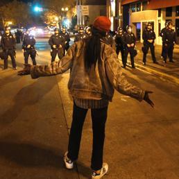 Un dimostrante sfida i poliziotti schierati in assetto anti-sommossa durante gli scontri scoppiati nella notte a Ferguson, nel Missouri, a seguito del proscioglimento dell'agente Darren Wilson che il 9 agosto scorso uccise con ripetuti colpi di pistola un ragazzo afroamericano disarmato di 18 anni, Michael Brown (Reuters)