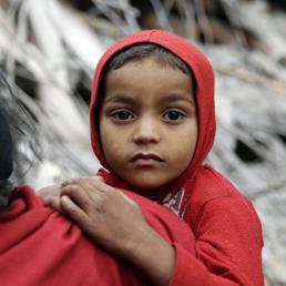 Un bambino nepalese come viene portato in braccio  tra le macerie degli edifici crollati a Kathmamdu dopo il terremoto (Epa) (EPA)