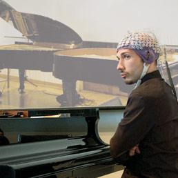 Orazio Sciortino. Nella foto il pianista con cuffia ed elettrodi qualche istante prima dell'improvvisazione-esperimento avvenuto a Roma. Insieme a lui si è esibito Richard Rentsch, compositore e pianista svizzero