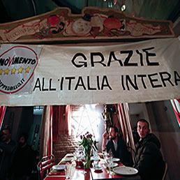 I sostenitori del Movimento 5 Stelle festeggiano in un ristorante il risultato del voto con uno striscione di ringraziamento agli elettori (Reuters)
