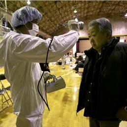 Un uomo è sottoposto allo screening per l'esposizione alle radiazioni in un rifugio dopo essere stato evacuato dalle zone circostanti gli impianti nucleari Fukushima (Ap)