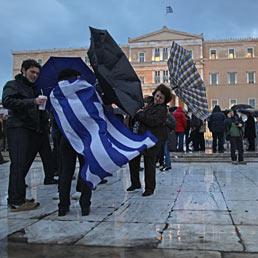 Fitch declassa la Grecia a «C». Nella foto alcuni manifestanti, con una bandiera greca, cercano di tenere gli ombrelli sotto la pioggia e le raffiche di vento, di fronte al parlamento greco durante una manifestazione di protesta ad Atene (AP Photo)