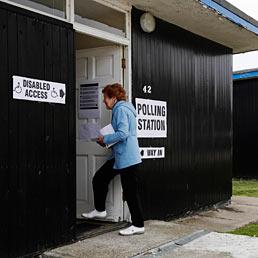 Nella foto una donna arriva entra in un seggio elettorale in uno chalet a Dymchurch, nel sud dell'Inghilterra (Reuters)