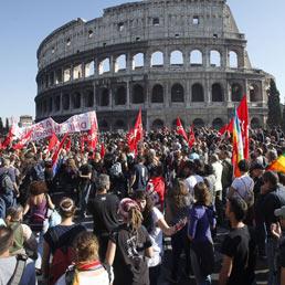 Il corteo dei manifestanti passa davanti al Colosseo (Ansa)
