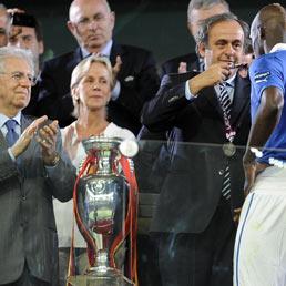 Il presidente Michel Platini con Mario Balotelli, mentre il premier italiano Mario Monti lo applaude durante la cerimonia di premiazione di Uefa Euro 2012 (Ansa)