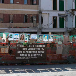 L'area dove sorgeva la Casa dello studente all'Aquila, con le foto degli otto ragazzi che morirono nel crollo del palazzo. (Ansa)