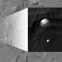 La capsula che contiene il rover marziano Curiosity sta arrivando sul suolo del pianta frenata dal più grande paracadute supersonico mai costruito. L'immagine presa dalla sonda NASA Mars Reconnaissance Orbiter, dotata di una eccezionale camera fotografica, HiRise.