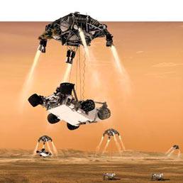 Le ultime fasi della discesa di Curiosity sul suolo marziano. Prima il paracadute supersonico rallenta la discesa e poi la gru spaziale lo fa atterrare dolcemente grazie ai retrorazzi.